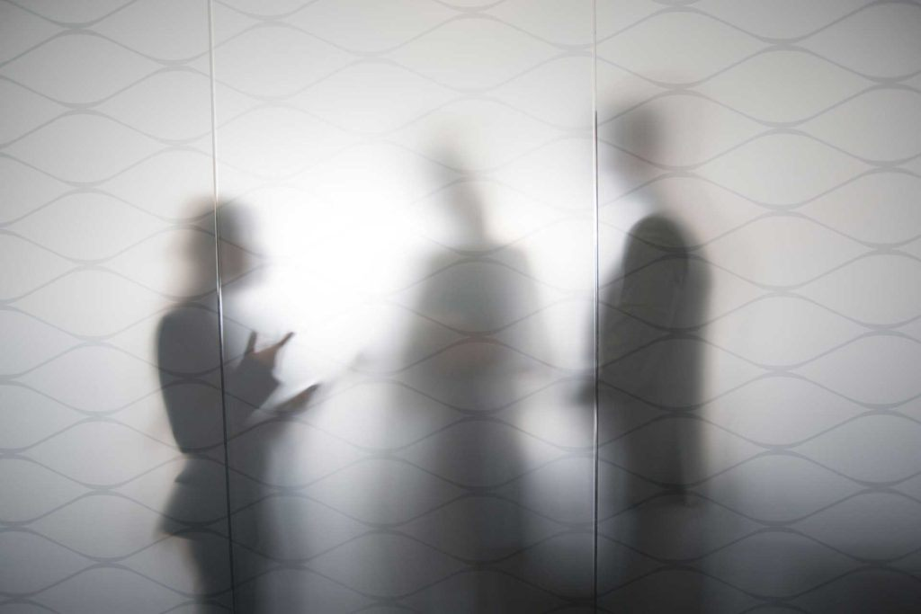 three silhouettes standing behind frosted glass